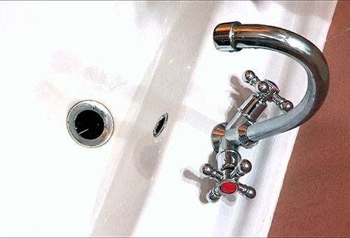 Кран и слив в ванной
