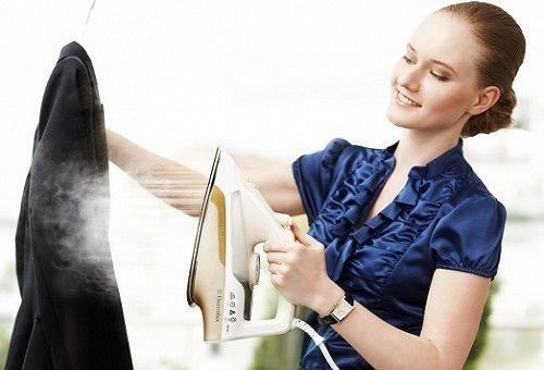 девушка чистит пальто утюгом