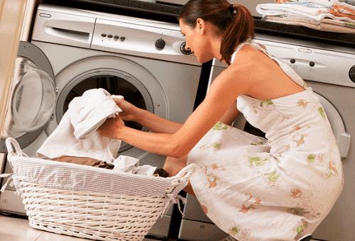 девушка загружает вещи в стиральную машину