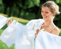 Девушка развешиввет белые вещи после стирки