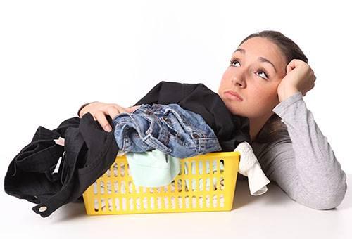 Девушка думает, как стирать джинсы и брюки