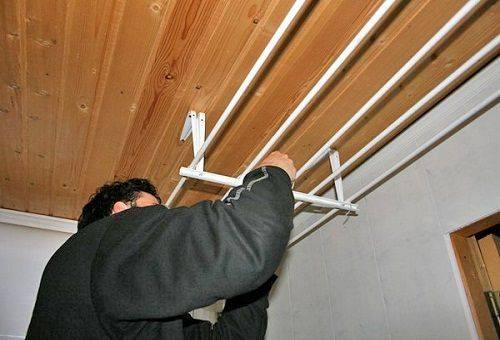мужчина прикрепляет сушилку для белья к потолку