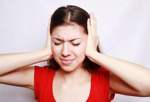 Молодая женщина закрывает ее уши