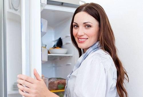 Девушка готовится к размораживанию холодильника