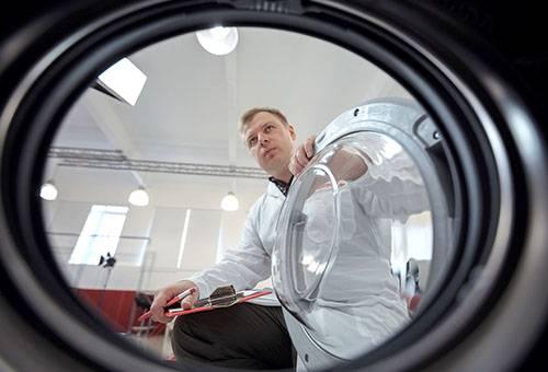Мужчина изучает стиральную машину