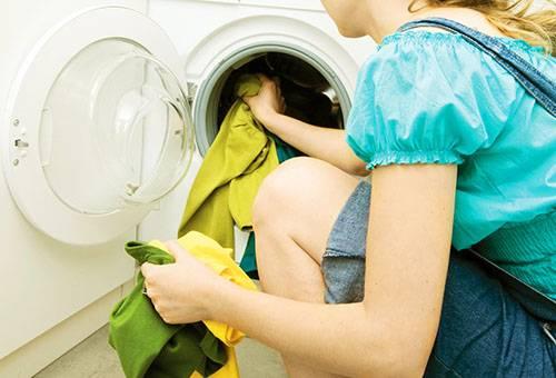 Женщина загружает белье в стиральную машину