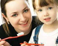 женщина с девочкой с зубными щетками в руке