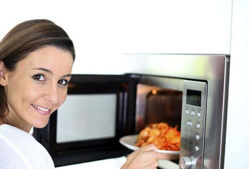 девушка разогревает еду в микроволновке