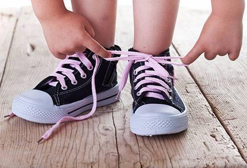 Ребенок завязывает шнурки на кедах