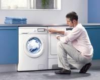 Мужчина проверяет работу стиральной машины