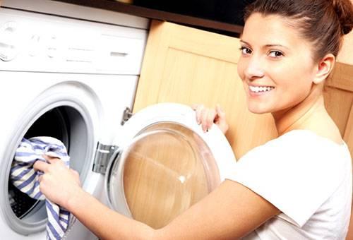 Девушка закладывает белье в стиральную машину