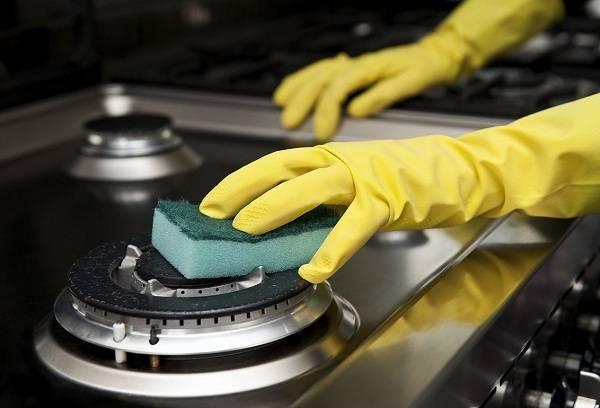 женщина чистит плиту