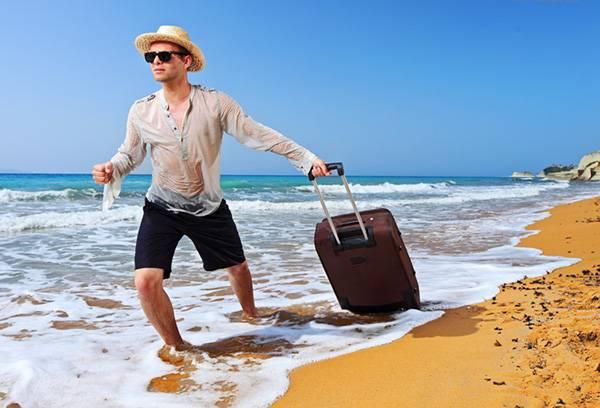 Мужчина на пляже с чемоданом