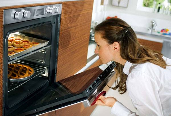 Женщина готовит выпечку в духовке