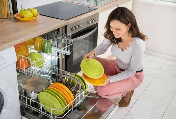 Девушка разгружает посудомойку
