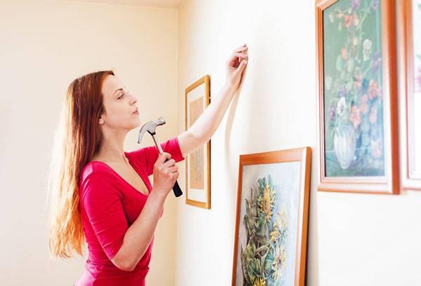 Девушка вешает картины