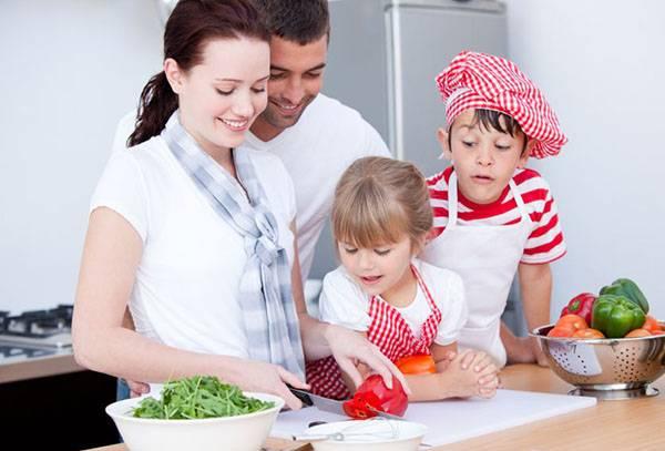 Семья на кухне готовит салат