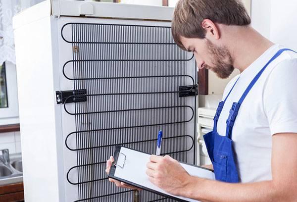 Мастер проводит диагностику холодильника