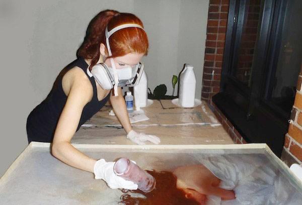 Девушка в респираторе работает с эпоксидной смолой