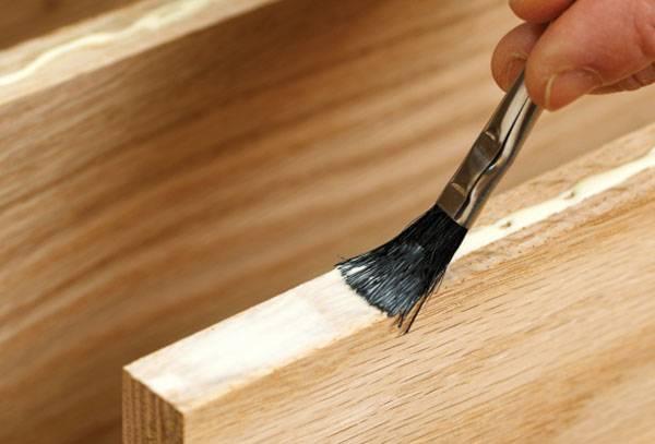 Нанесение клея на деревянный элемент мебели