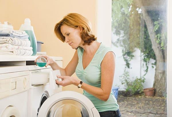Женщина заливает кондиционер в стиральную машину