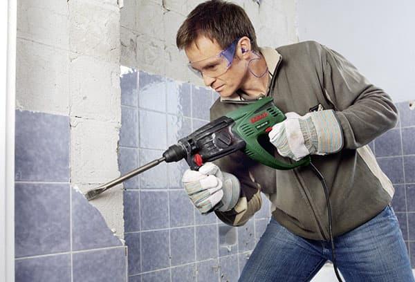 Мужчина удаляет плитку со стены перфоратором