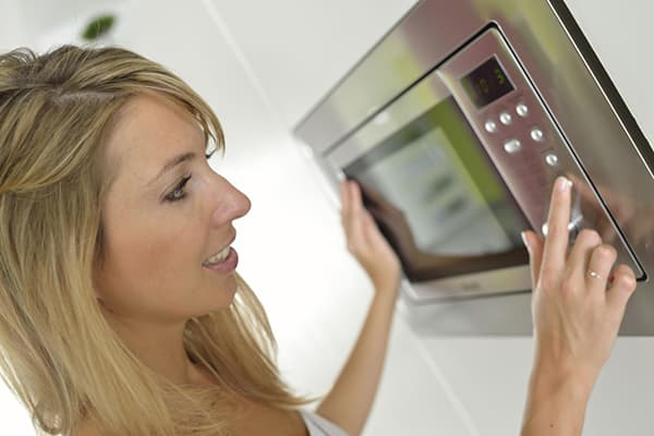 Девушка готовит в микроволновке