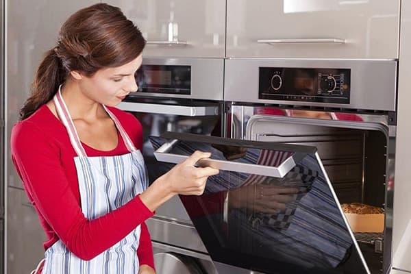 Девушка готовит пирог в духовке