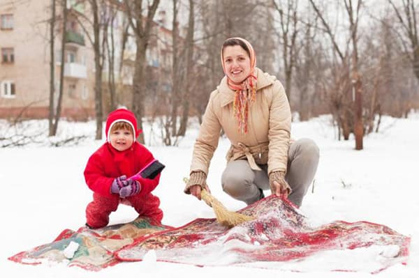 Женщина с ребенком чистят ковер в снегу