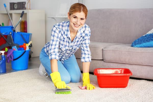 Женщина чистит светлый ковер