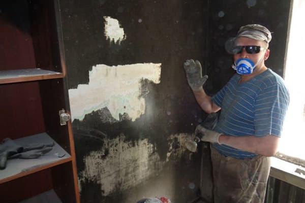 Мужчина счищает копоть со стены после пожара