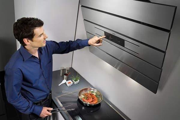 Мужчина включает вытяжку над плитой