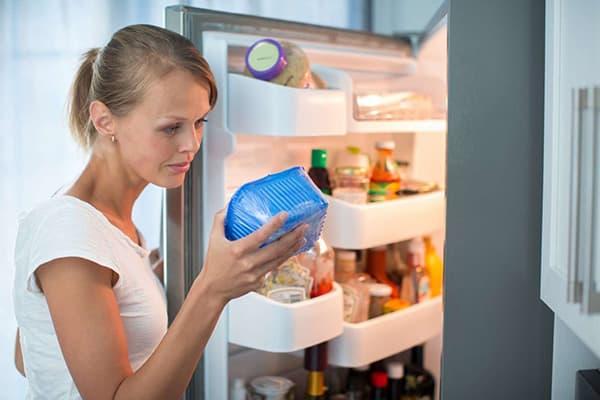 Девушка проводит ревизию в холодильнике