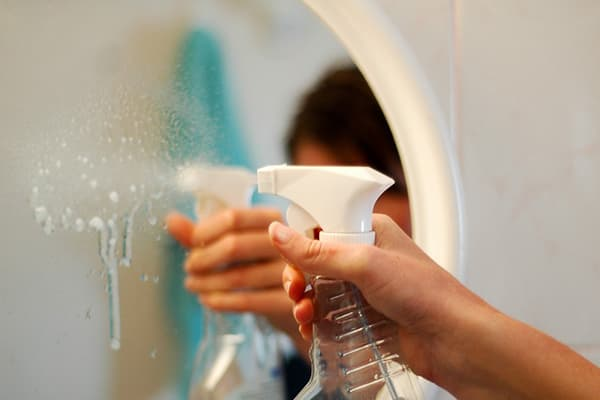 Распыление моющего средства на зеркало