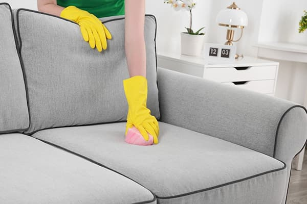 Женщина чистит диван
