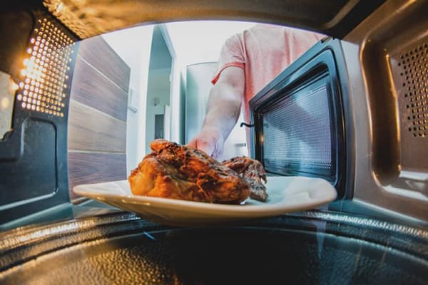 Мужчина ставит мясо в микроволновку