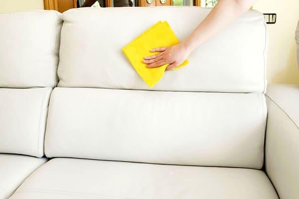 Женщина протирает диван салфеткой