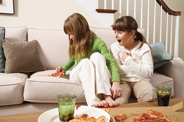 Девочка уронила кусок пиццы на диван