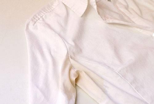 Желтое пятно от пота на белой рубашке
