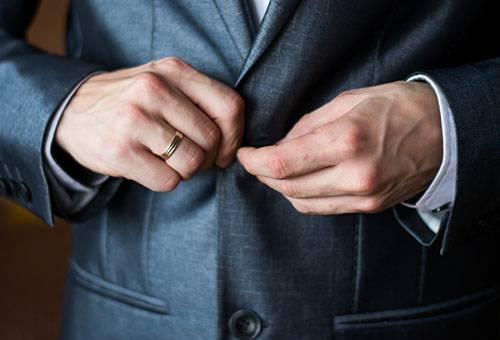 Мужчина застегивает пиджак