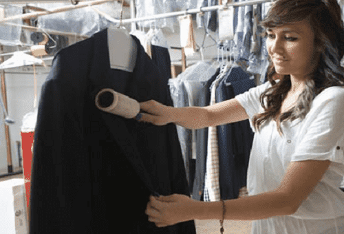 девушка чистит пальто от пыли