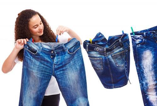 Девушка развешивает джинсы для сушки