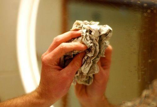 женщина моет зеркало газетой