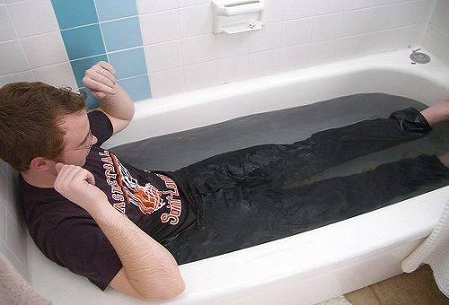 мужчина в ванной в джинсах