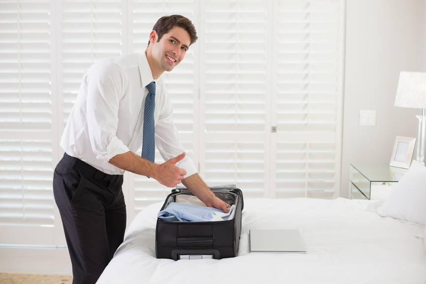 Мужчина кладет в чемодан сложенную рубашку