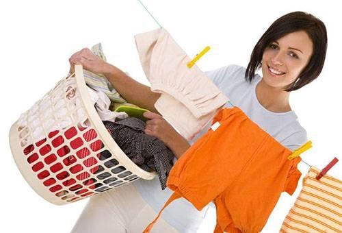 Женщина развешивает постиранную одежду