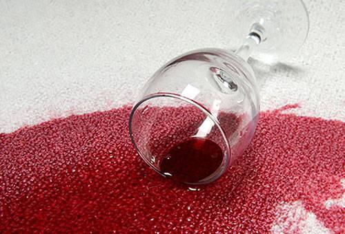 Разлитое вино на светлом ковре