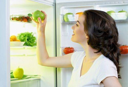девушка с яблоком у холодильника