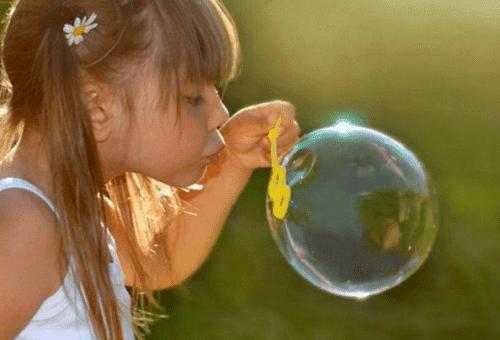 девочка надувает мыльный пузырь