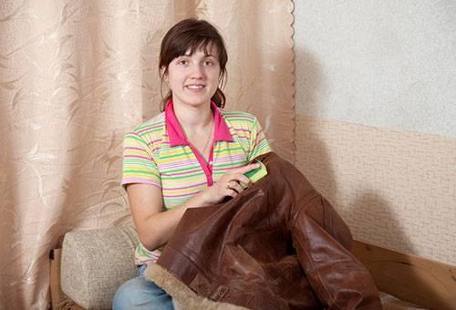Женщина чистит кожаную куртку